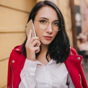 Close-up portrait of lovely black-haired girl in red jacket posing with smartphone on city background. Outdoor shot of female office worker in white shirt talking on phone.